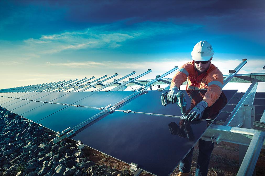 WOrker installing solar panels on farm