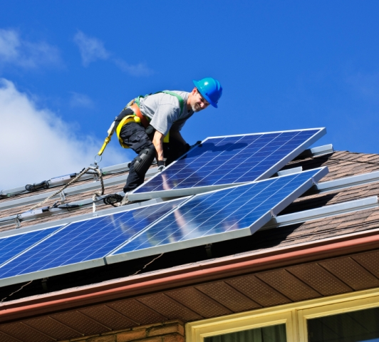 Worker installing solar panels on roof