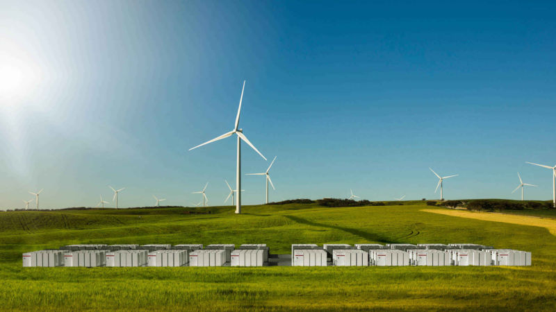Tesla batteries wind turbines in the background