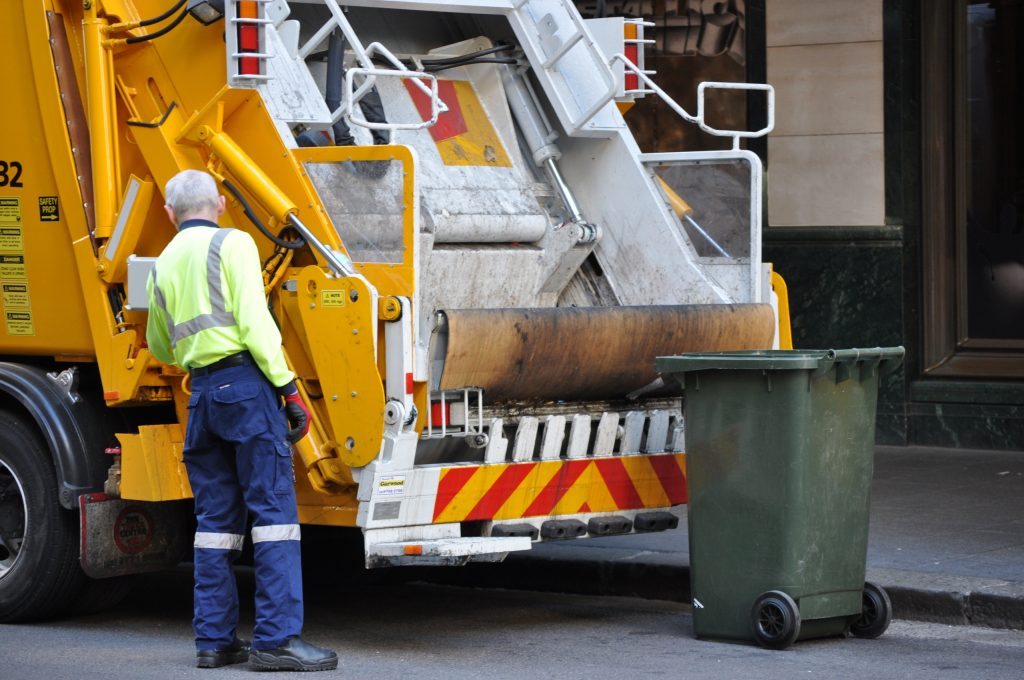 A garbage truck driver working emptying rubbish into his truck