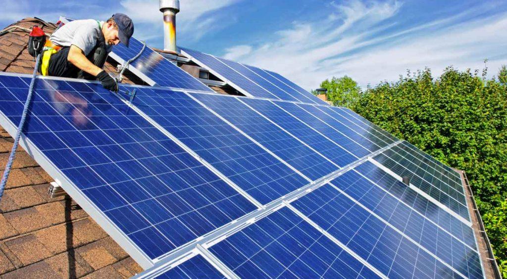Worker installing rooftop solar panels