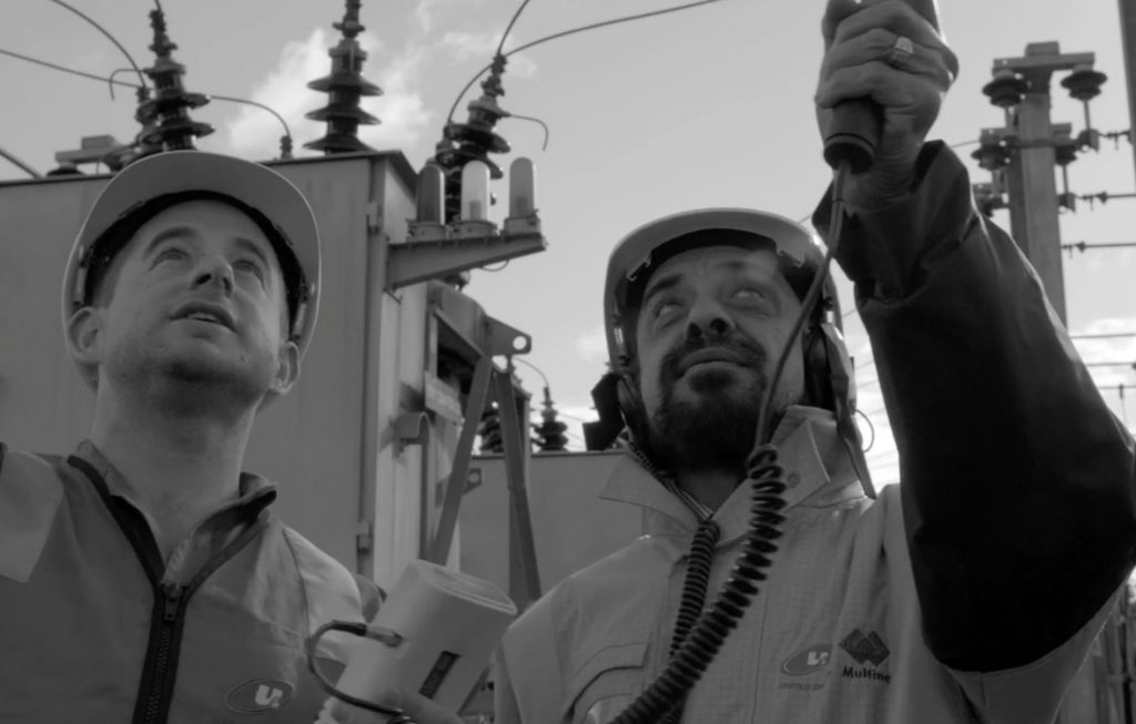 Two workers near transmission lines