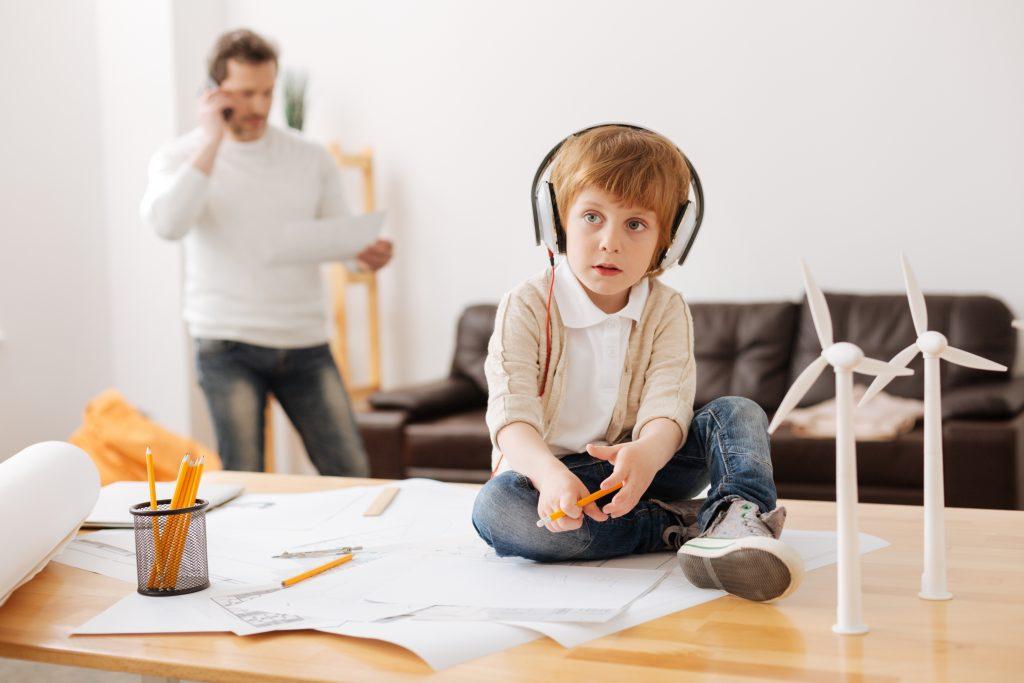 Child listening to headphones next to wind turbine models