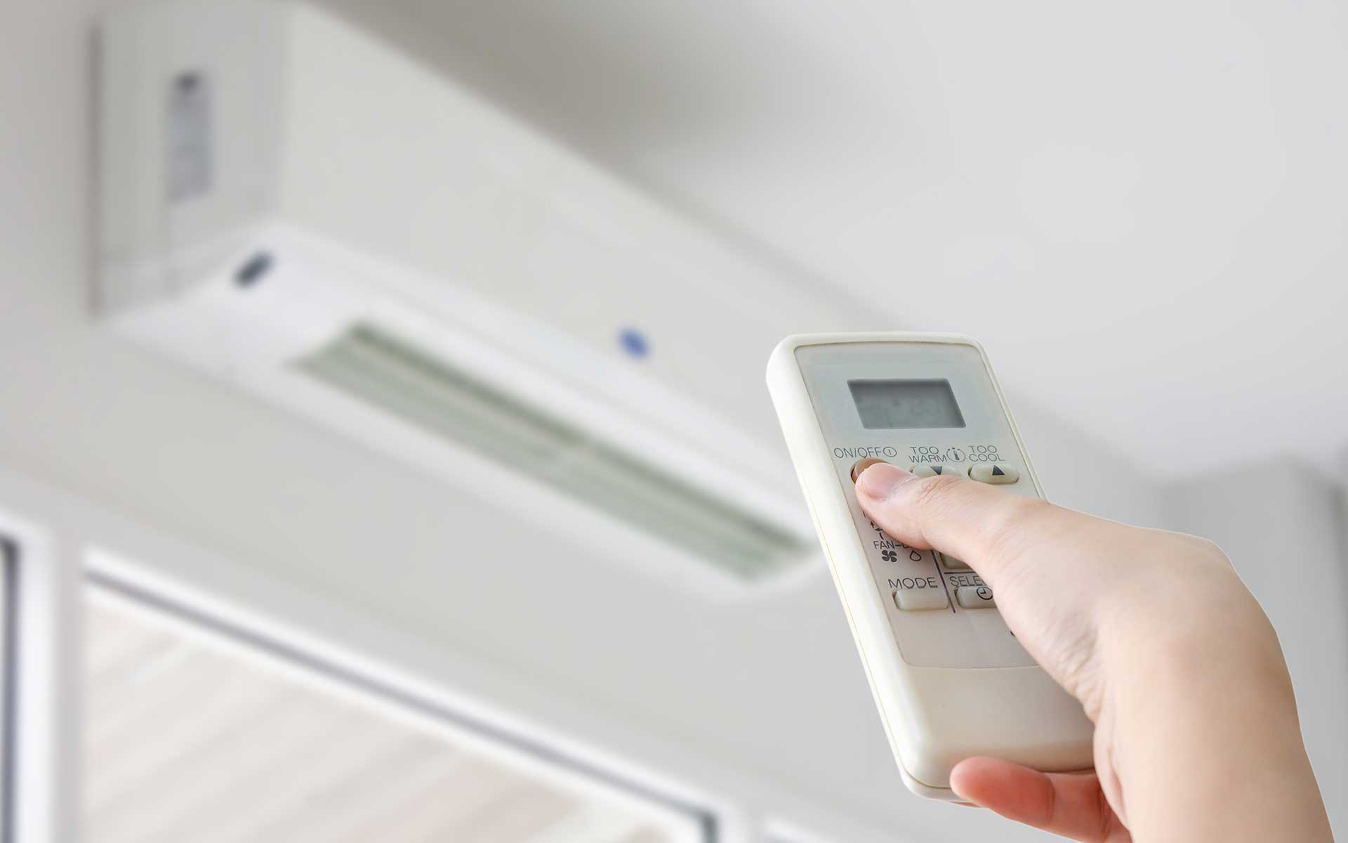 Image - Person using remote control to power on a heating and cooling unit