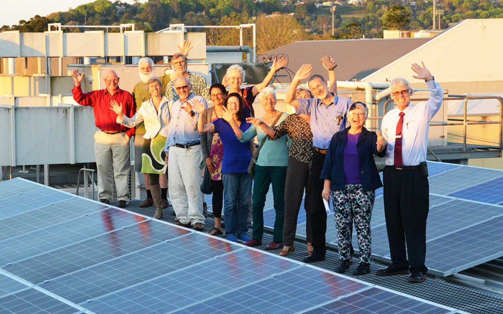 People waving in front of solar panels to be used in the Social Access Solar Gardens project