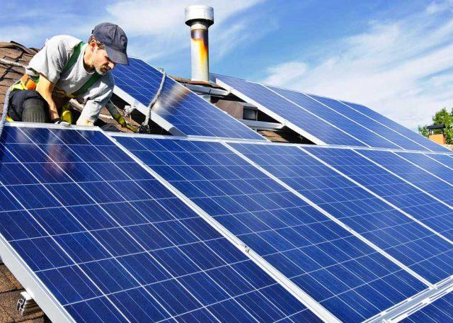 Worker installing solar panels on suburban roof
