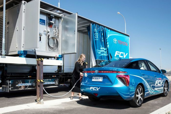 Woman refuelling electric vehicle at Toyota's portable station