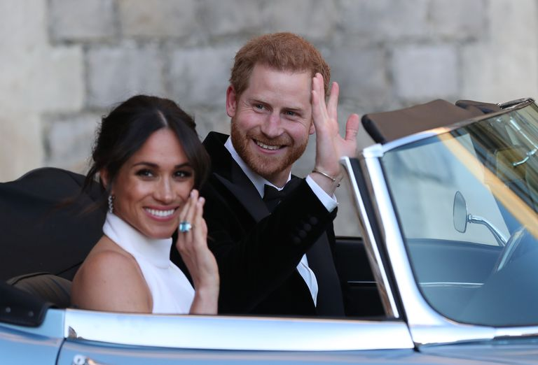 Prince Harry and Meghan Markle ride in an electric vehicle