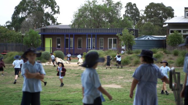 Children playing in the school yard with the HIVVE portable classroom in the background