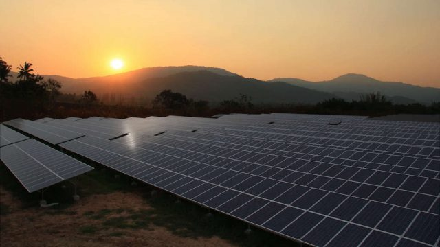 Large-scale solar farm with sun setting behind it