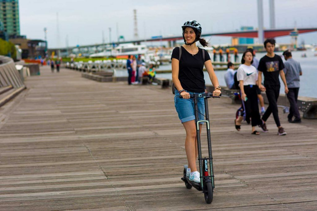 Woman riding on Raine electric scooter at Docklands Pier