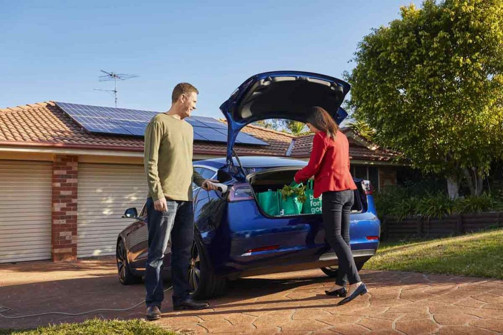 Man charging his electric vehicle while his wife unloads the groceries